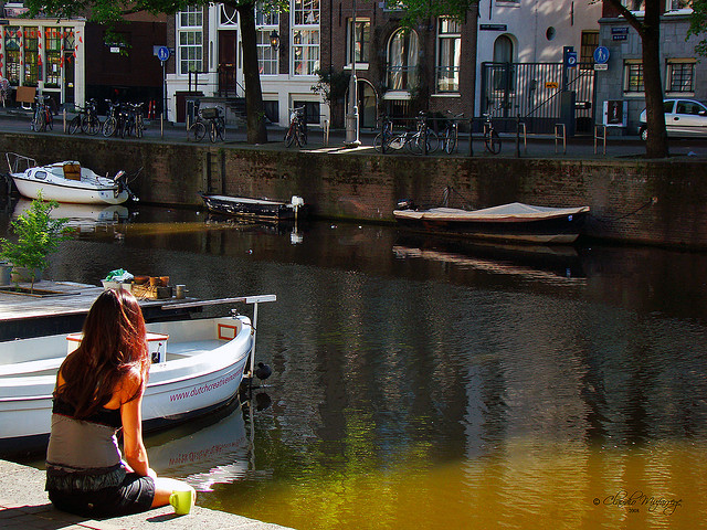 girl sitting on canal in Amsterdam