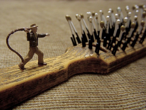small indiana jones toy figurine attacking a hairbrush