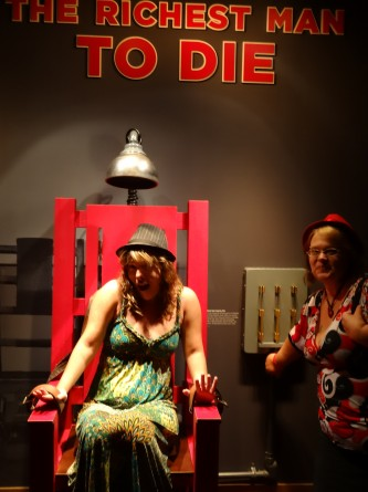 girl pretending to be electrocuted in chair in mob museum las vegas