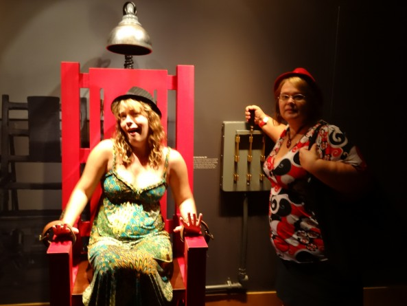 girl sitting in fake electric chair and woman pulling the lever at the mob museum in las vegas