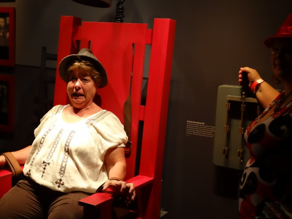 woman sitting in fake electric chair in mob museum in las vegas