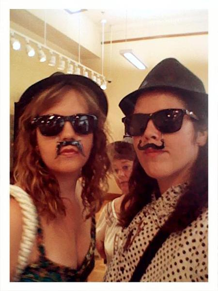 two girls with glasses and fake moustaches