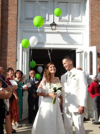 bride and groom leaving church and releasing balloons