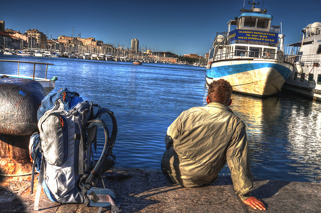 backpacker sitting on the dock of a bay