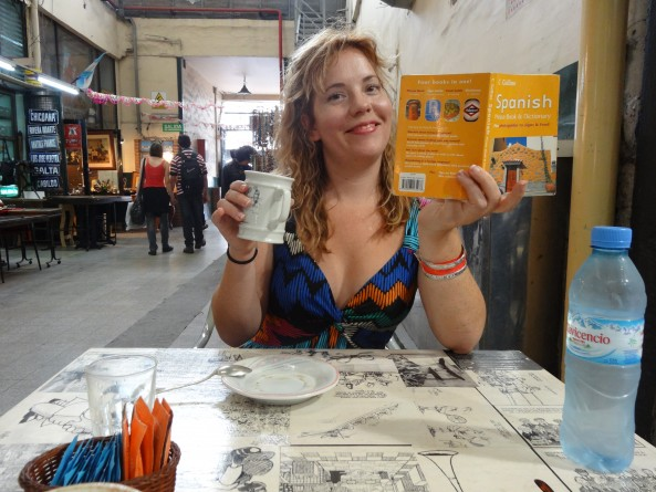 reannon sipping coffee and reading a Spanish language phrase book in buenos aires
