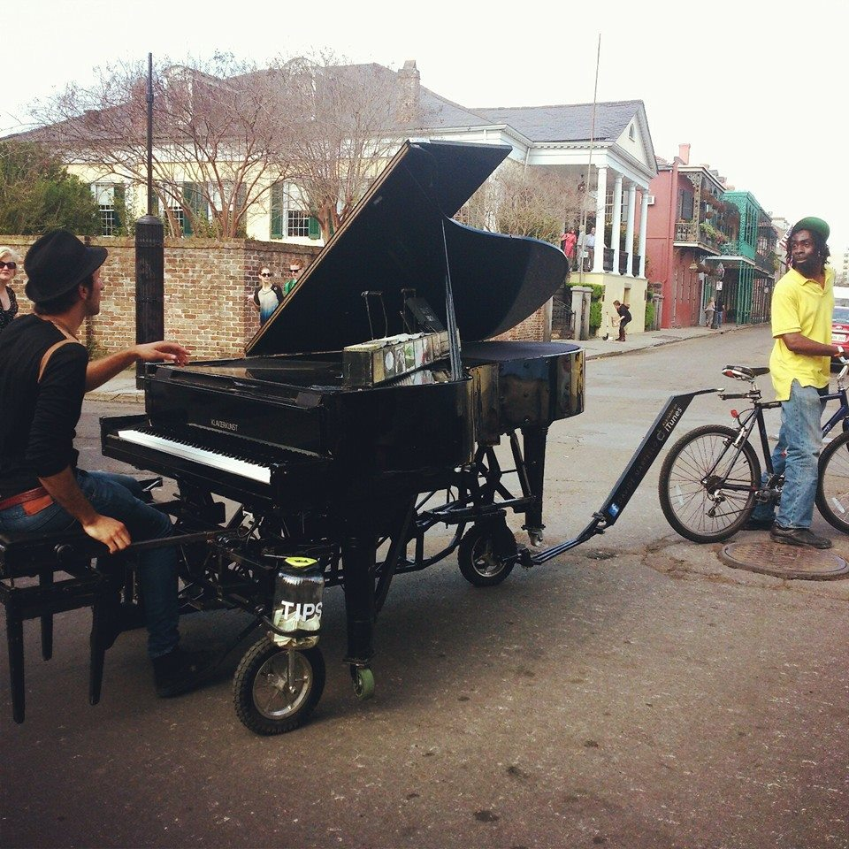 man playing piano while friend tows him on a bike